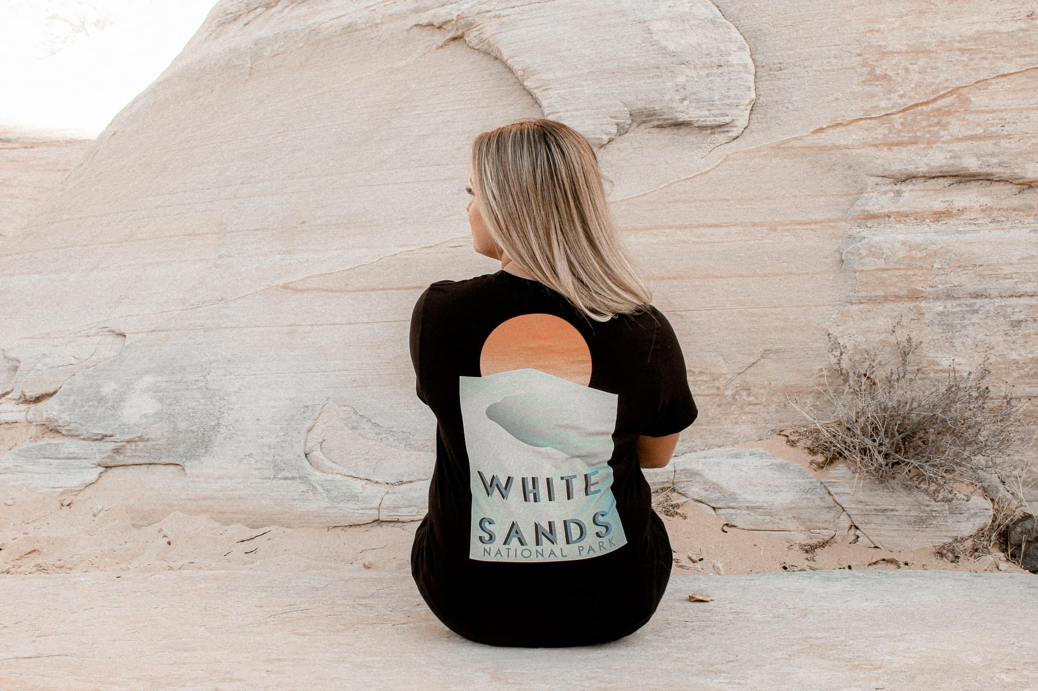 female leaning against a rock with a White Sands National Park shirt and blue jeans