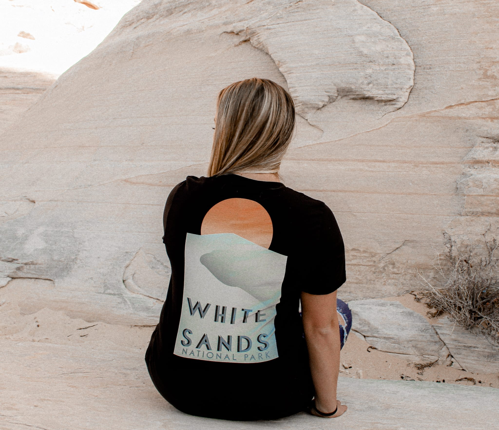 Female sitting against a rock with a white sands national park t-shirt