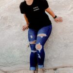 Female leaning against a rock with a white sands national park t-shirt and khaki pants