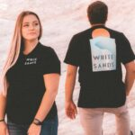 Male and female walking on a large rock with white sands national park t-shirts