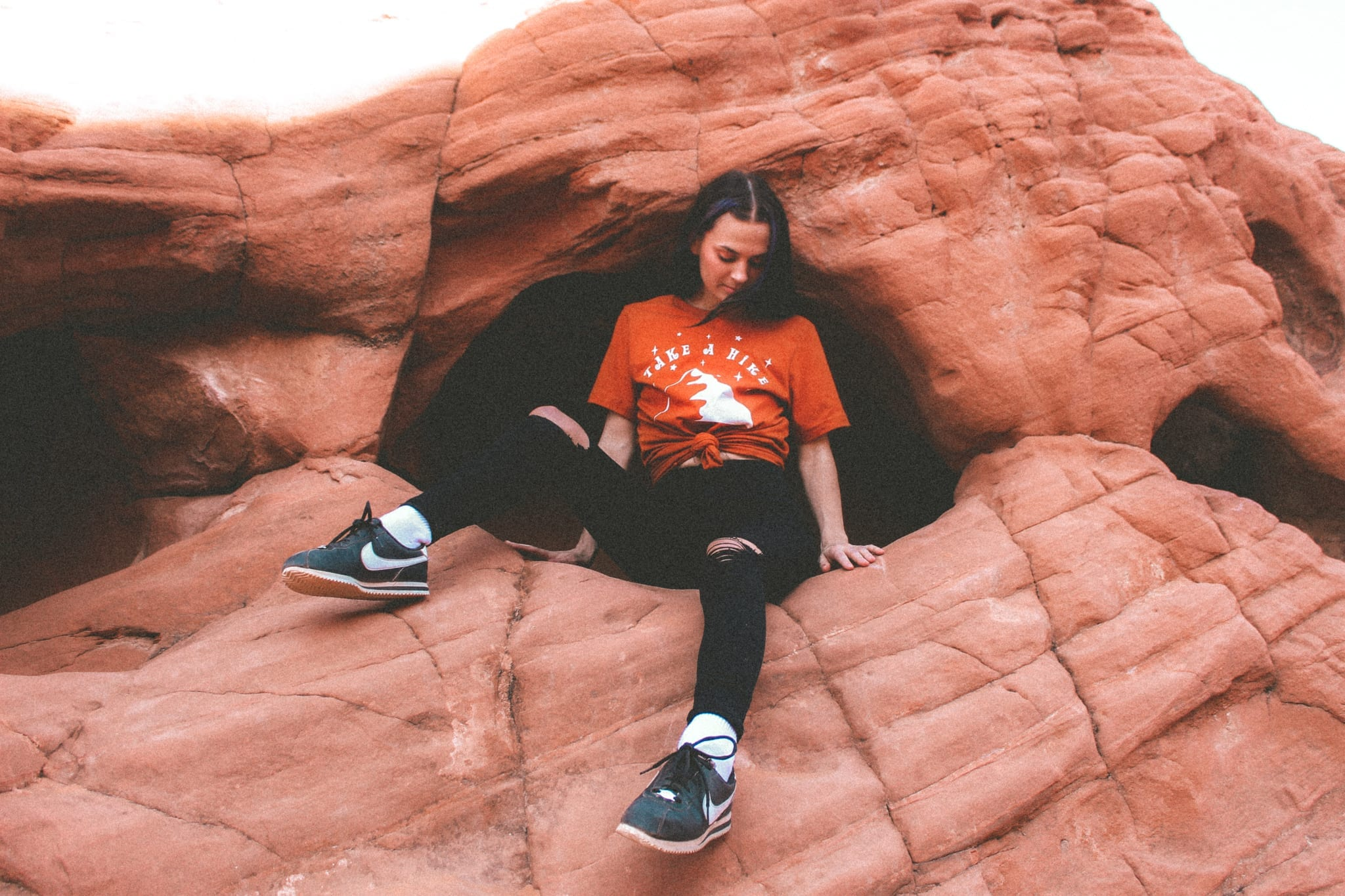 woman sitting in a hole in the side of a large rock