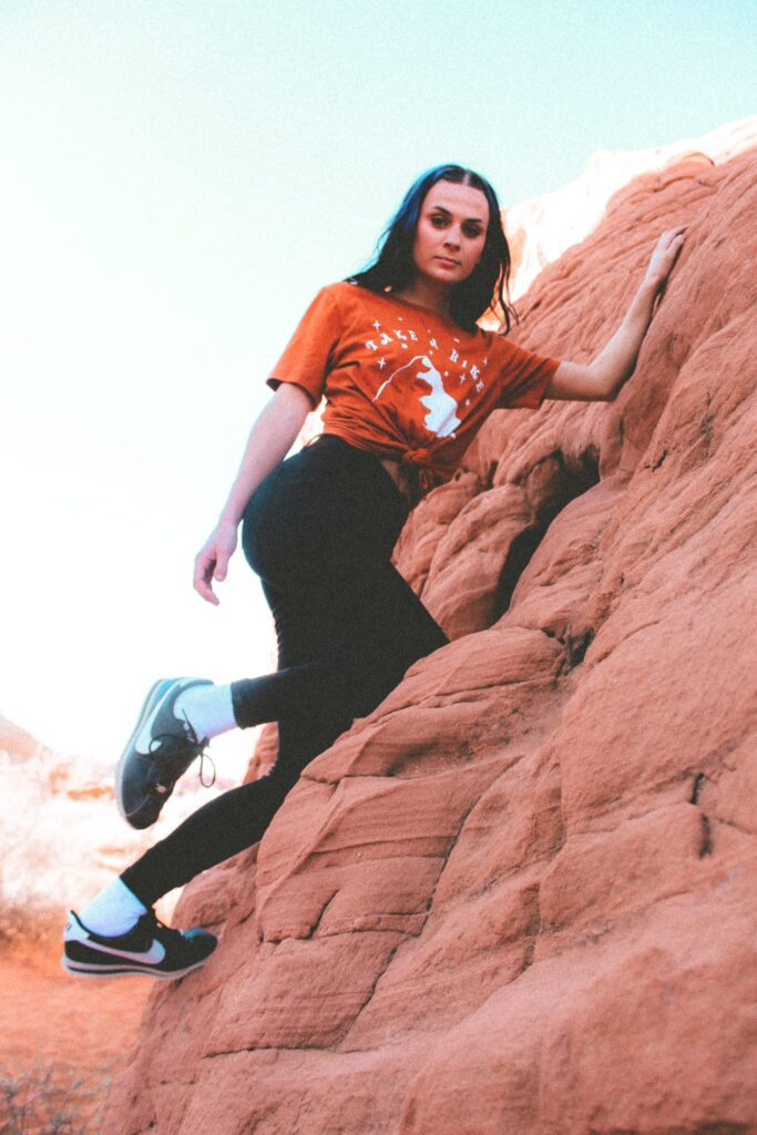 one female climbing a red rock