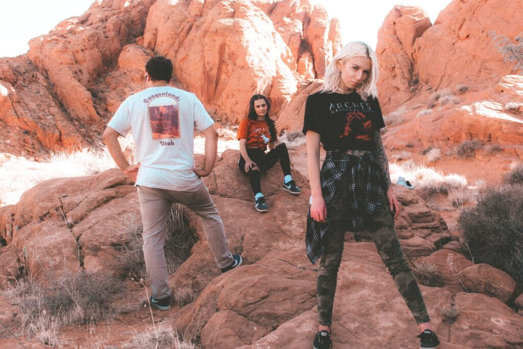 two women and one male in a valley of red rocks