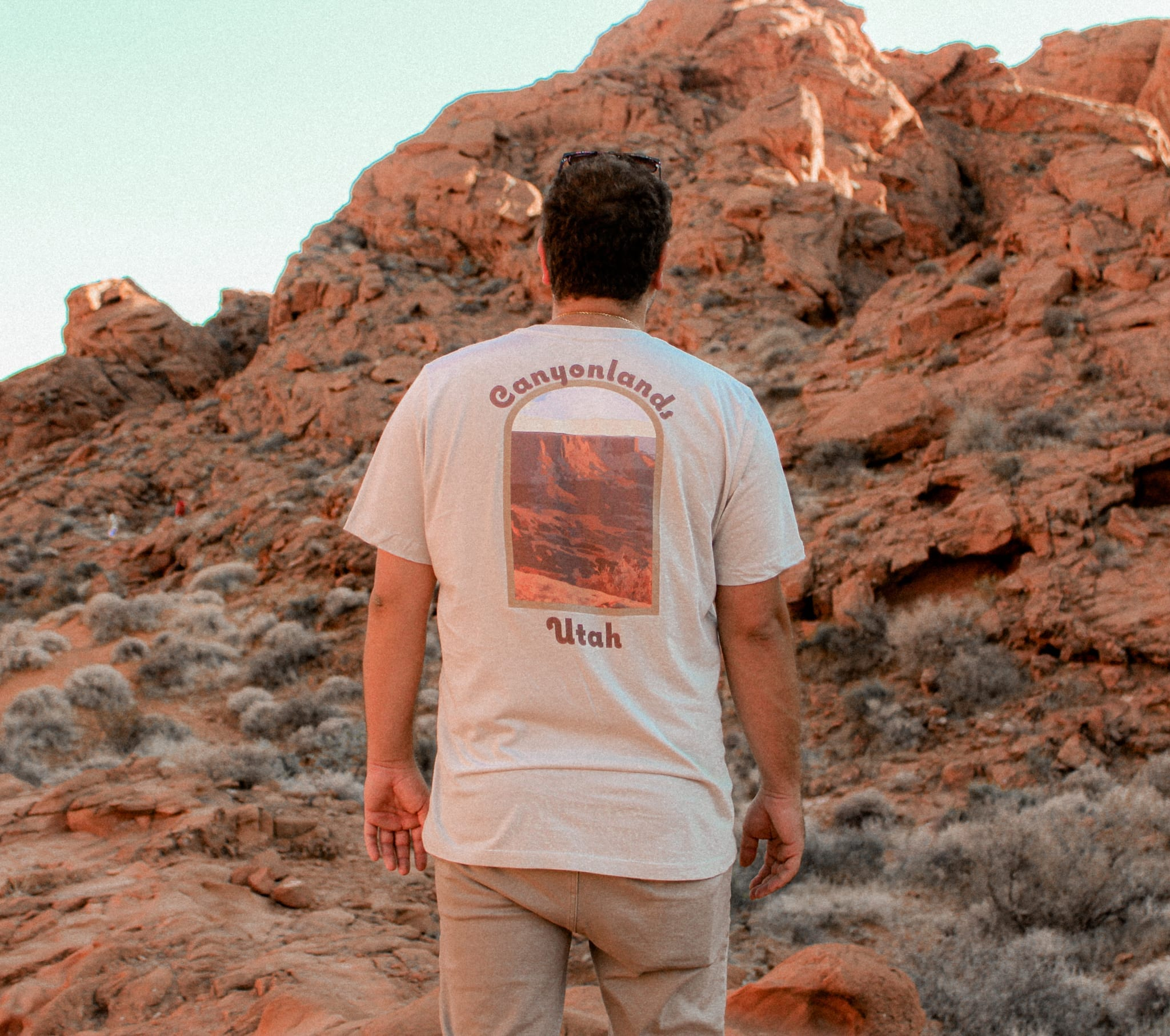 male gazing over a valley of red rocks wearing a cream colored canyonlands t-shirt