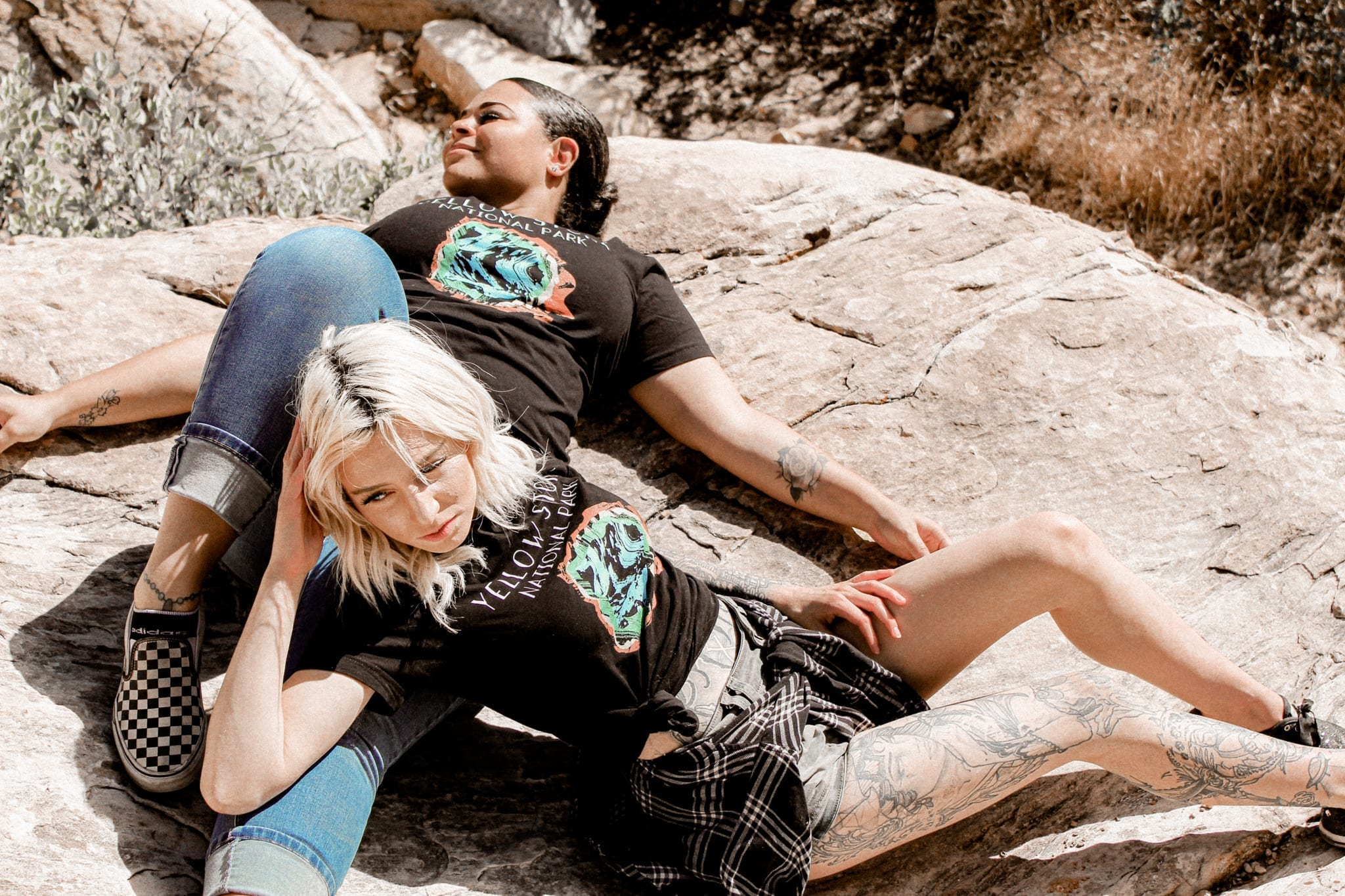 two females laying next to eachother in the mountains with a black yellowstone national park shirt