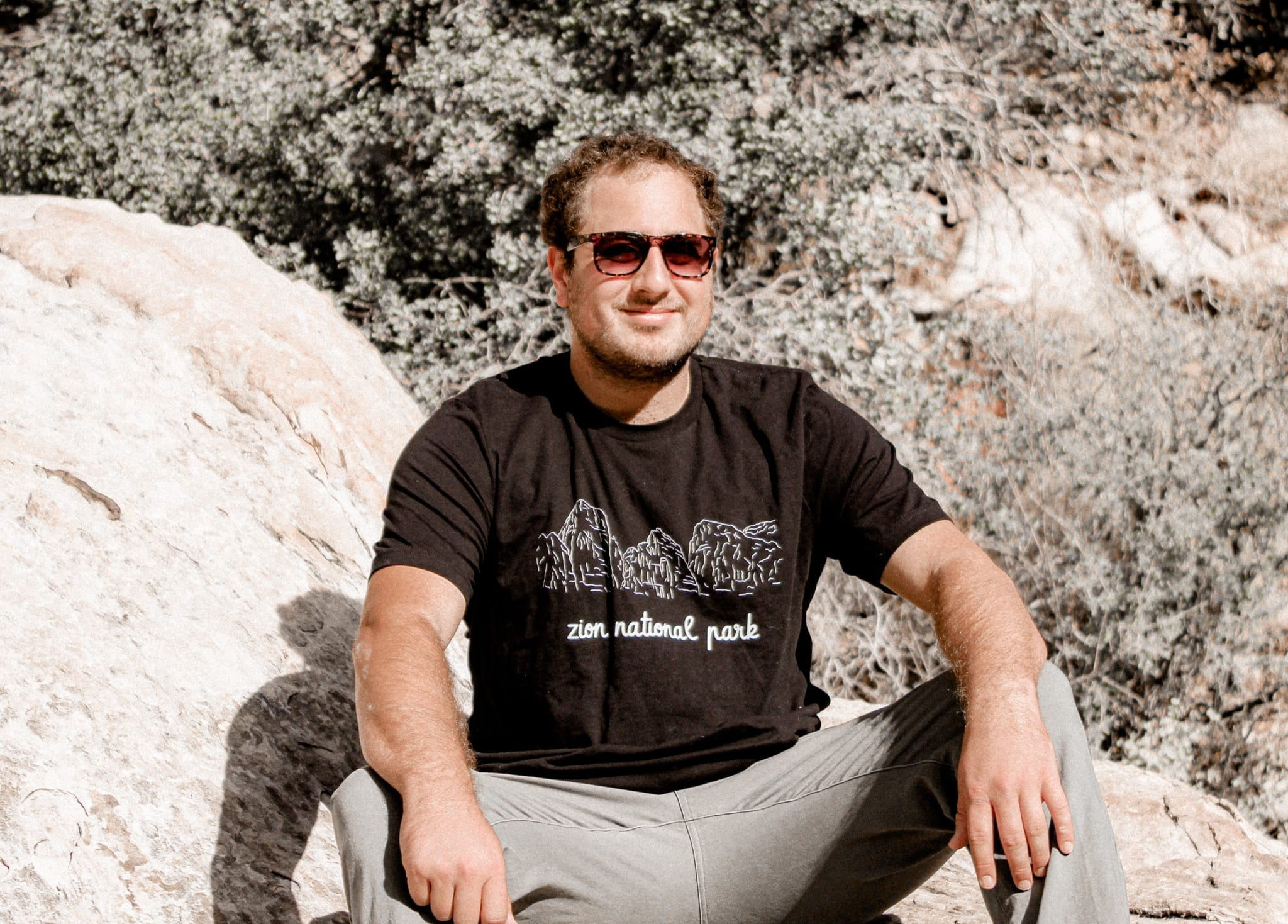 Male sitting on rock with zion national park black t-shirt