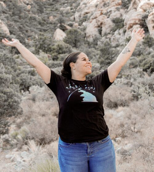 female with a black take a hike shirt with green hills behind her