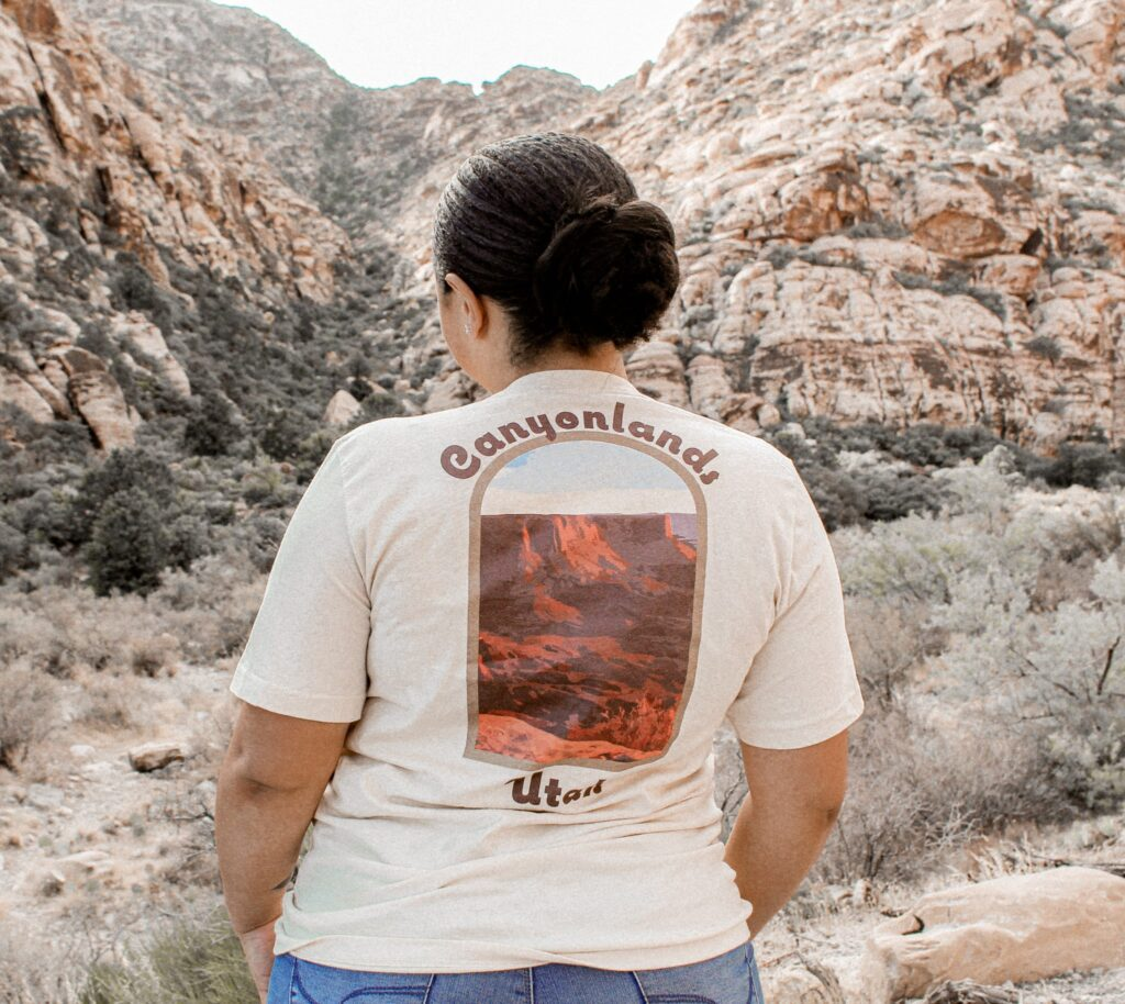 woman standing in a green valley in a cream colored canyonlands t-shirt