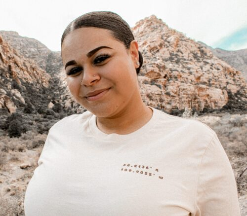 woman wearing a t-shirt with canyonlands coordinates with green hills behind her
