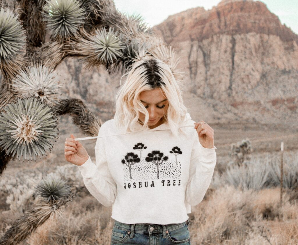 female standing next to a joshua tree with mountains in the background wearing a joshua tree hoodie